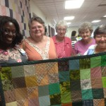 First Lutheran Blanket Sewers Present Lap Quilts to Susan Achieng-Jenkins, Director of Lutheran Care Center's Adult Day Program